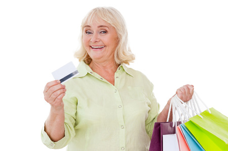 I love shopping! Happy senior woman showing her credit card and holding shopping bags while standing isolated on white background Stok Fotoğraf