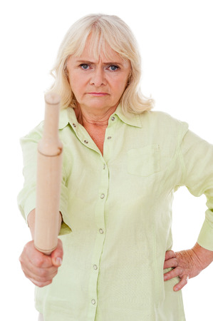 one senior woman only: Senior woman with rolling pin. Angry senior woman holding rolling pin and looking at camera while standing isolated on white background