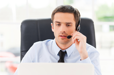 Operator at work. Confident young man looking at laptop and adjusting his headset while sitting at his working place Stock Photo