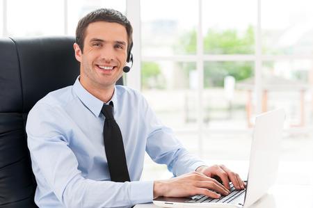 Vrolijke mannelijke operator. Zijaanzicht van vrolijke jonge man in headset kijken naar de camera en glimlachen terwijl met behulp van laptop