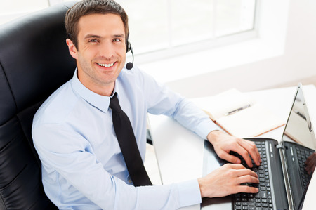 computer support: IT support. Top view of cheerful young man in headset looking at camera and smiling while using laptop