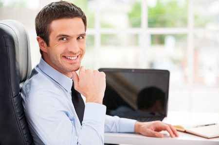 Confident and successful. Handsome young man in formalwear looking over shoulder and smiling while sitting at his working place photo
