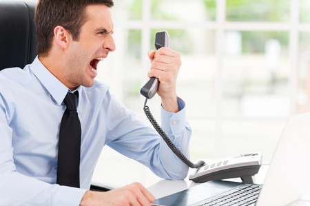 expressing negativity: I want this report now! Furious young man in shirt and tie shouting at the telephone while sitting at his working place Stock Photo