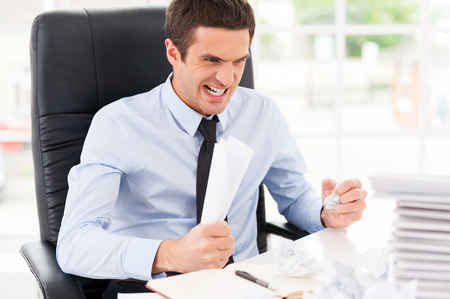 office physical pressure paper: Sick and tired. Furious young man in shirt and tie holding papers in hands and shouting while sitting at his working place Stock Photo
