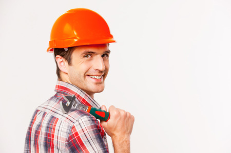 Handyman with wrench. Rear view of handsome young handyman with carrying wrench on shoulder and looking over shoulder while standing against grey background photo