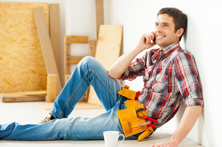 Handyman relaxing. Handsome young handyman talking on the mobile phone and smiling while sitting on the floor  photo