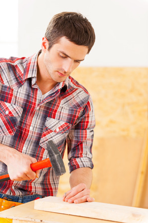 Hammering a nail. Handsome young handyman hammering a nail to a wooden deck