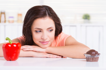 what to eat: Sweet temptation. Thoughtful young woman choosing what to eat while leaning at the kitchen table with chocolate muffin and fresh pepper laying on it