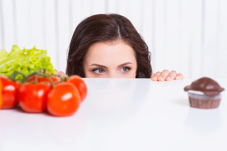 binge: What to choose? Thoughtful young woman looking out of the table while fresh vegetables and chocolate muffin laying on it  Stock Photo