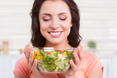 Fresh and healthy salad. Portrait of beautiful young woman holding a bowl with salad and looking at it with smile while standing in the kitchen  photo