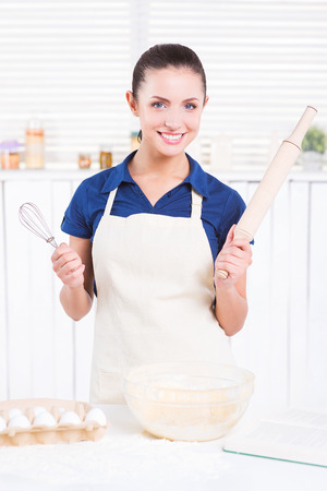 wire whisk: Ready for cooking. Cheerful young woman in apron holding rolling pin and wire whisk while standing in a kitchen