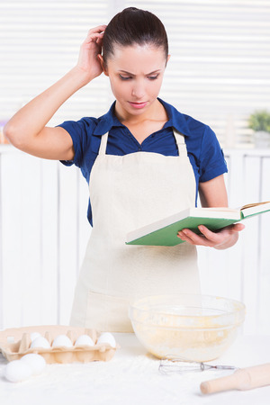 wire pin: What am I doing wrong? Cheerful young woman in apron holding rolling pin and wire whisk while standing in a kitchen