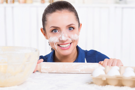 Messy cooking. Playful young woman with flavor on face holding rolling pin and looking out of the kitchen table  photo