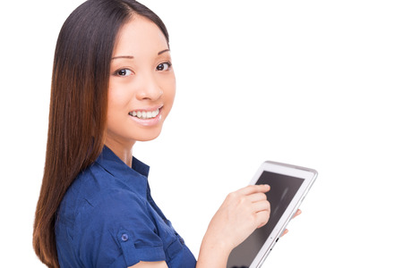 Taking advantages of digital age. Rear view of beautiful young Asian woman using digital tablet and looking over shoulder while standing isolated on white photo