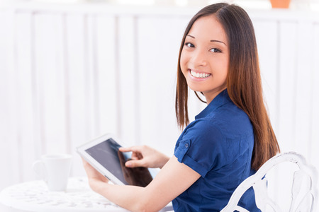 over the shoulder view: Surfing web in cafe. Rear view of beautiful young Asian woman using digital tablet and looking over shoulder while sitting in cafe Stock Photo