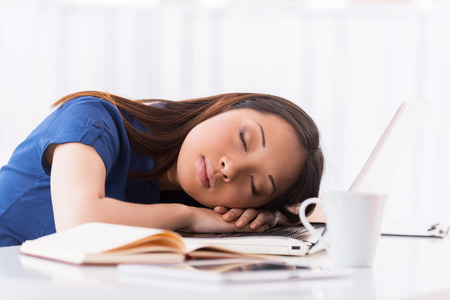 working place: Sleeping at working place. Beautiful young Asian woman sleeping at her working place Stock Photo
