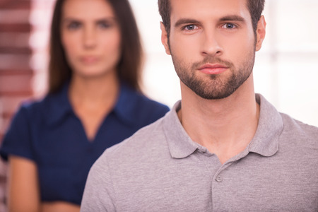man behind: Young and successful. Confident young man looking at camera while woman standing behind him and keeping arms crossed