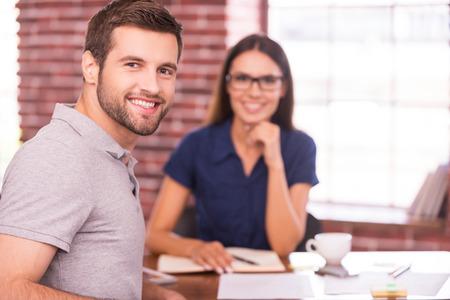 interview job: Candidato del trabajo. Apuesto joven sentado en la mesa y mirando por encima del hombro con una sonrisa mientras que la mujer alegre que se sienta delante de �l