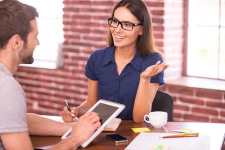 Het bespreken van zaken. Twee vrolijke mensen uit het bedrijfsleven in vrijetijdskleding praten en gebaren tijdens de vergadering op de tafel Stockfoto
