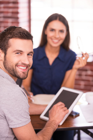 foreground focus: Young and creative colleagues. Two cheerful business people in casual wear sitting at the table together and looking at camera while man holding digital tablet  Stock Photo