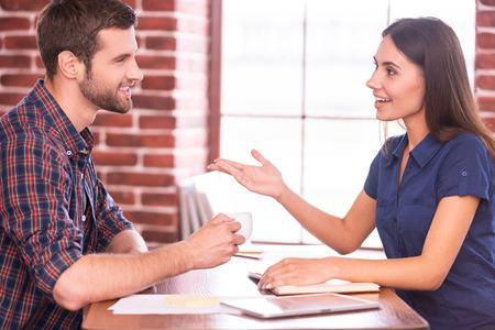 Collega's op koffiepauze. Zijaanzicht van vrolijke jonge man en vrouw zitten aan de tafel en chatten tijdens man met kopje warme drank