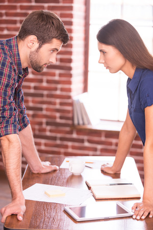 battle of the sexes: Business confrontation. Side view image of angry man and woman standing face to face while leaning at the office table  Stock Photo