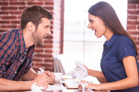 sexes: Battle of the sexes. Side view image of angry man and woman sitting face to face at the office table and shouting at each other