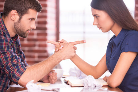 sexes: Blaming each other. Side view image of angry man and woman sitting face to face at the office table and pointing each other