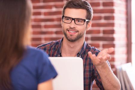 Bedrijfs bespreking. Twee bedrijfsmensen in vrijetijdskleding praten en glimlachen tijdens de vergadering van aangezicht tot aangezicht aan tafel