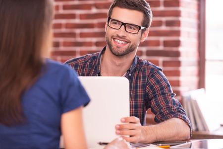Zakelijke communicatie. Twee zaken mensen in vrijetijdskleding praten en glimlachen tijdens de vergadering van aangezicht tot aangezicht aan tafel
