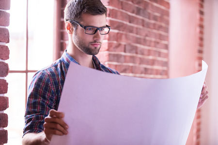 home improvement: Architect examining blueprint. Confident young man in glasses examining blueprint while standing near the window Stock Photo