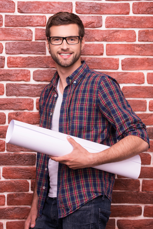 brown: Confident architect. Handsome young man in glasses holding blueprint and smiling while standing against brick wall