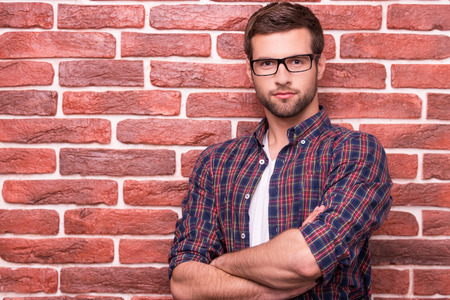 Charming handsome. Handsome young man keeping arms crossed and looking at camera while standing against brick wall Banco de Imagens