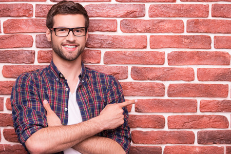 only adult: Confident handsome pointing your advertising. Handsome young man keeping arms crossed and pointing at copy space while standing against brick wall