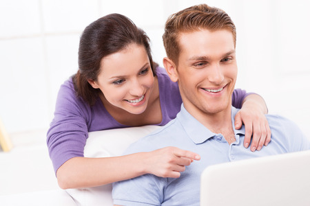 Look at that! Cheerful young loving couple sitting on the couch and looking at laptop while woman pointing monitor and smiling photo