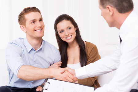 customer relationship: Sealing a deal. Happy young man shaking hand to financial agent while sitting together with his wife Stock Photo