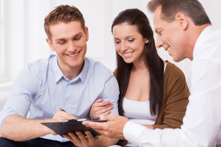 Just sign here. Happy young couple signing documents while confident mature man holding clipboard and smiling   photo