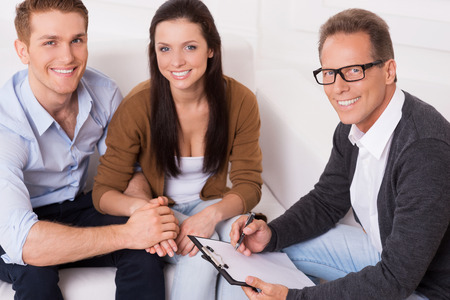 Family therapy . Top view of happy young couple and confident psychiatrist sitting together and smiling photo