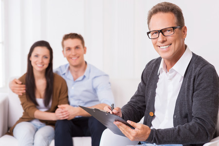 Confident family psychologist. Confident psychiatrist writing something in clipboard and smiling while cheerful couple sitting in the background and holding hands  photo