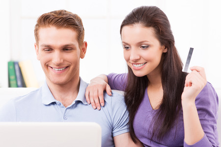 Online shopping. Beautiful young loving couple shopping online while sitting on the couch together photo