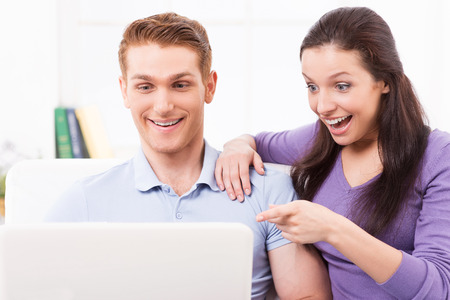 Just look at that! Surprised young loving couple sitting on the couch and looking at laptop while woman pointing monitor photo