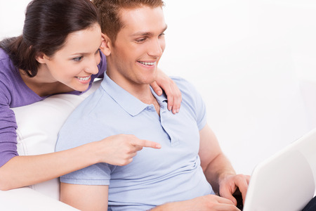 Can you believe it! Cheerful young loving couple sitting on the couch and looking at laptop while woman pointing monitor and smiling photo