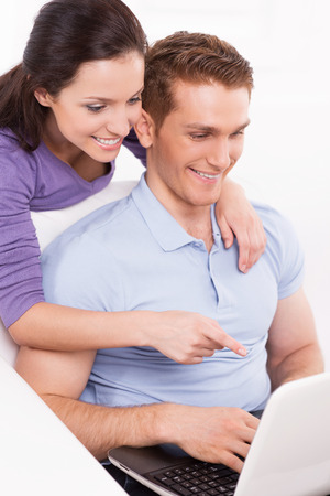Surfing the net together. Happy young loving couple sitting on the couch and looking at laptop while woman pointing monitor and smiling photo