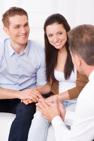 Listening to an expert advice. Happy young couple discussing financial matter with financial consultant  photo
