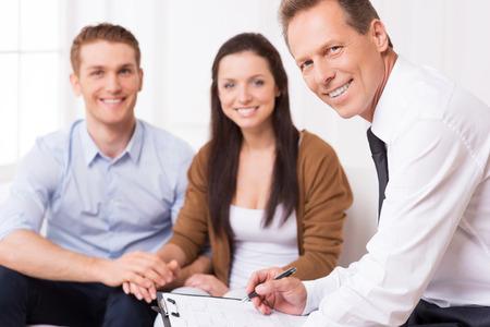 Zelfverzekerd financieel expert. Zelfverzekerde volwassen man in overhemd en das kijken naar de camera en glimlachen terwijl paar zitten in de achtergrond en lachend