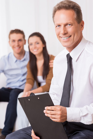 legal advice: Confident financial expert. Confident mature man in shirt and tie holding clipboard and looking at camera while couple sitting in the background and smiling  Stock Photo