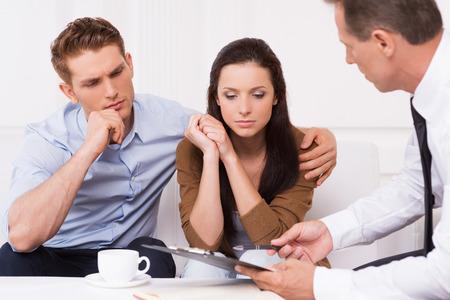 Deskundig advies. Doordachte jonge paar zittend op de bank, terwijl vertrouwen financieel adviseur iets uit te leggen en te wijzen klembord Stockfoto