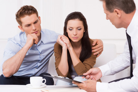 financial agreement: Expert advice. Thoughtful young couple sitting on the couch while confident financial advisor explaining something and pointing clipboard