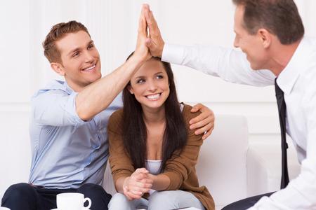 planificación familiar: Tenemos un trato. Hombre joven feliz aplaudiendo las manos con el agente financiero mientras se está sentado junto a su esposa