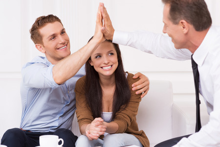 financial planning married: We have a deal. Happy young man clapping hands with financial agent while sitting together with his wife Stock Photo
